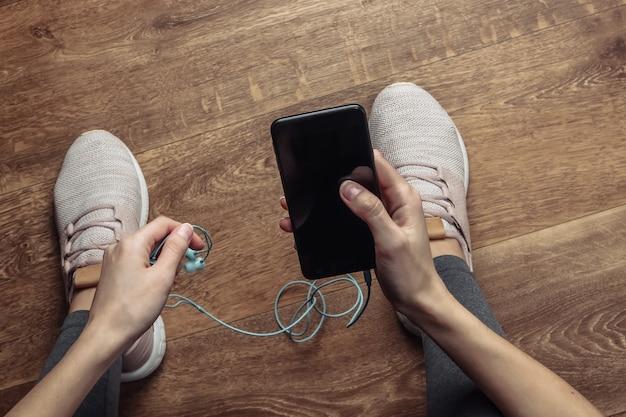 방 바닥에 앉아 운동복을 입은 여성은 미래의 운동이나 조깅을 위해 이어폰이 달린 스마트 폰에서 음악을 선택합니다.