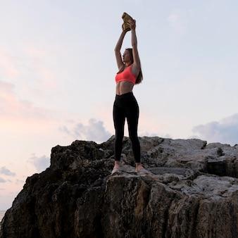 Женщина в спортивной одежде, стоя на берегу с поднятыми руками