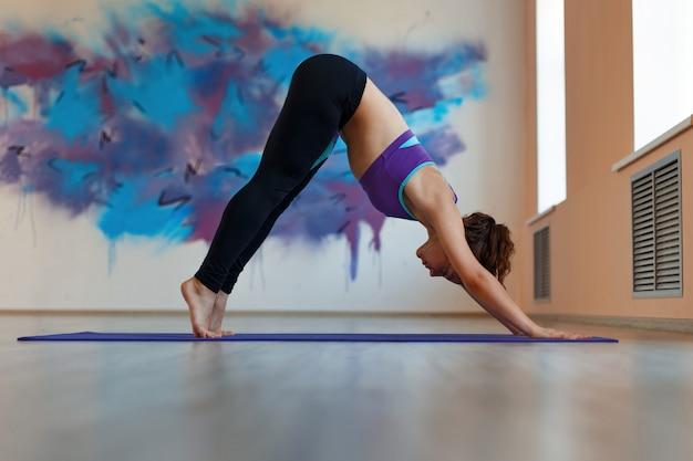 スポーツウェアの女性は筋肉を伸ばす