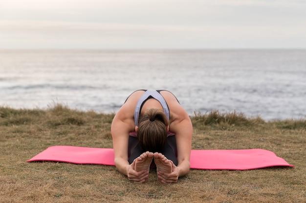 海とピンクのマットで屋外ストレッチスポーツウェアの女性