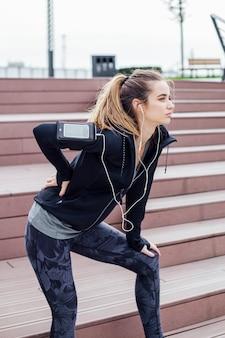 トレーニング後に背中の痛みに苦しんでいるスポーツウェアの女性