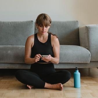 コロナウイルス検疫中に携帯電話を使用しているスポーツウェアの女性