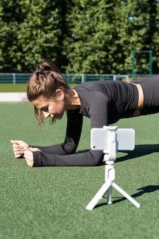 屋外の人工芝に座っているスポーツウェアvloggerの女性