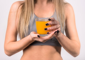 Woman in sportswear with glass of juice