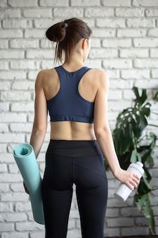スポーツ用品を持ち、ジムでのトレーニング後に魔法瓶を持っているスポーツウェアの女性。スポーツと健康的なライフスタイルのコンセプト。