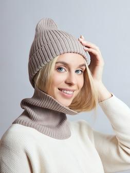 春の服を着た女性、スヌードのスカーフ、帽子、手袋。その女の子は金髪で青い目をしている
