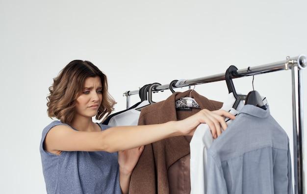 店内の女性は洋服シャツファッションスタイルのワードローブを選びます。