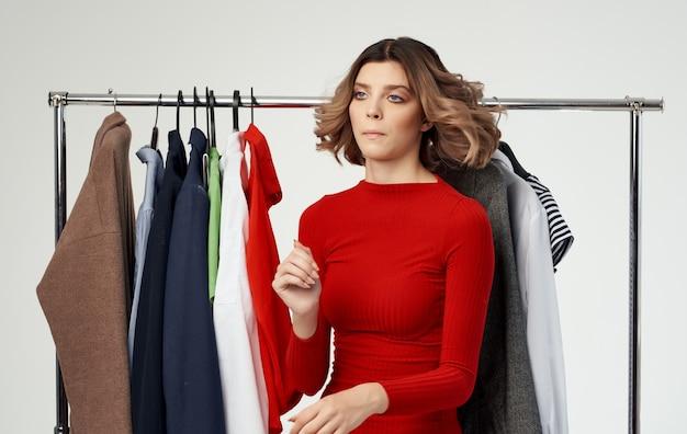 洋服のワードローブの赤いセーターシャツモデルと店内の女性。