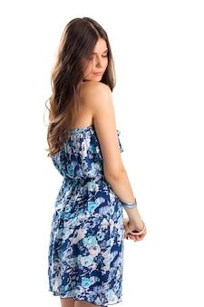 끈이 없는 꽃무늬 드레스를 입은 여자. 소녀는 어깨 너머로 다시 보인다. 여름용 가벼운 면 소재 의류. 매력적인 패션 모델.