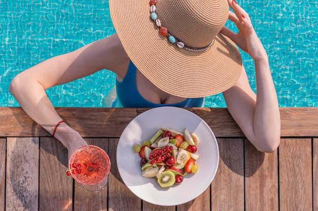 밀짚 모자와 수영장 근처 딸기와 비키니 입은 여자