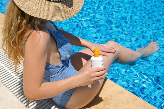 리조트에서 태양 보호 크림 선탠 수영장을 적용하는 밀짚 모자에있는 여자