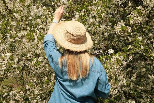 咲く春の庭で麦わら帽子の女性。晴れた春の日