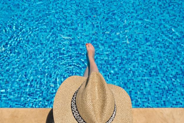 Женщина в соломенной шляпе загорает, сидя на краю бассейна
