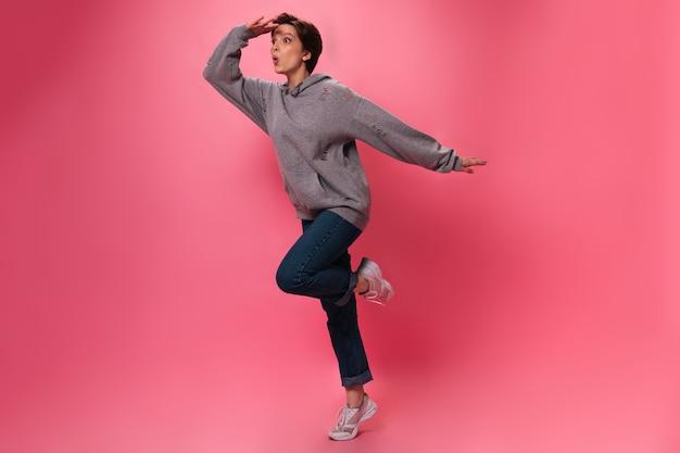 ストリートスタイルの服を着た女性は、ピンクの背景で距離を調べます。ジーンズとパーカーのアクティブな十代の少女が孤立してジャンプ
