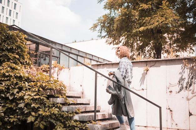 계단에 서있는 거리 착용에 여자