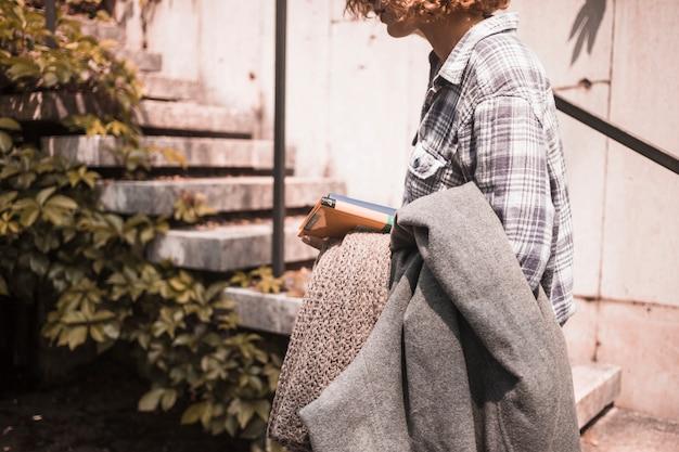 계단 근처 손에 책과 스카프로 거리 착용 여자