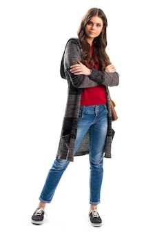 줄무늬 겉옷을 입은 여자. 청바지와 스웨터 코트. 팔짱을 낀 젊은 모델. 룩북의 새로운 의상 아이템.