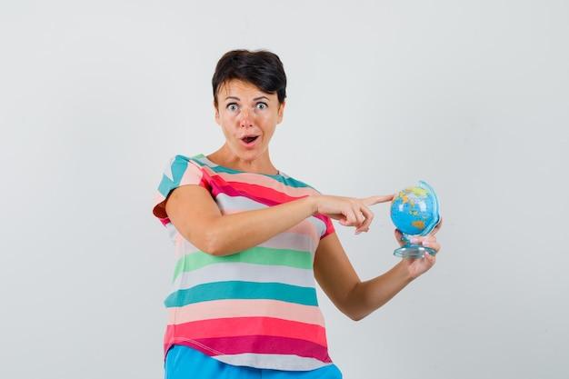縞模様のtシャツを着た女性、地球儀のモデルに指を保持し、驚いて見えるパンツ