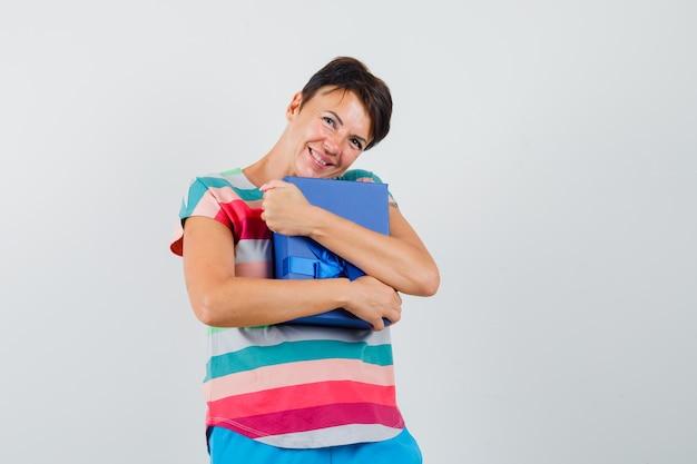 Женщина в полосатой футболке, штаны обнимает подарочную коробку и выглядит мило