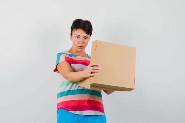 Женщина в полосатой футболке, штанах смотрит в картонную коробку и удивленно смотрит