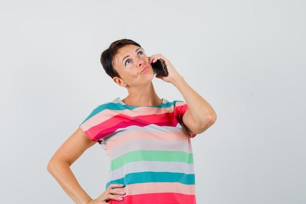 携帯電話で話し、物思いにふける縞模様のtシャツの女性