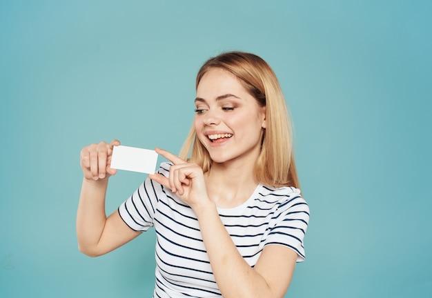 Женщина в полосатой футболке с кредитной картой на синем фоне обрезанный вид
