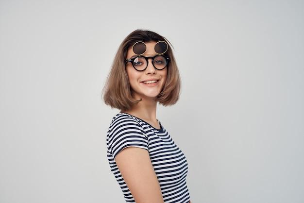 Женщина в полосатой футболке модные очки студия позирует