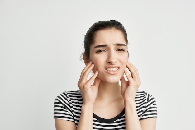 Женщина в полосатой футболке держит лицо недовольство зубной болью