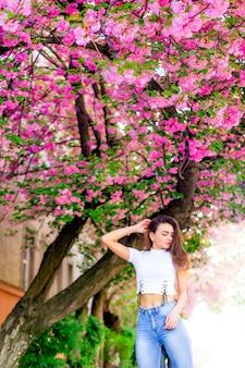 スタイリッシュな服を着た女性が日本の桜の木の近くで髪に手をかざす