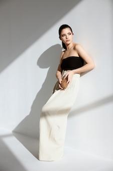 Женщина в стильной одежде присела на корточки и прислонилась к стене