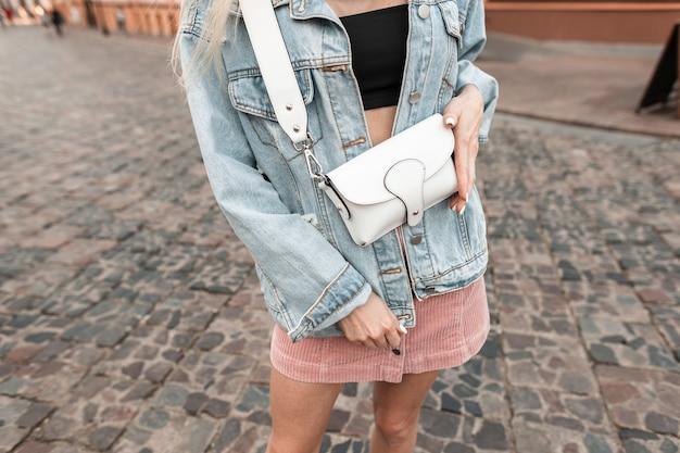 도시에서 세련된 가방을 들고 분홍색 치마를 입은 세련된 데님 재킷을 입은 여성