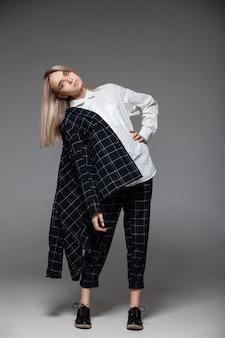 スタジオに立っているスタイリッシュな衣装の女性