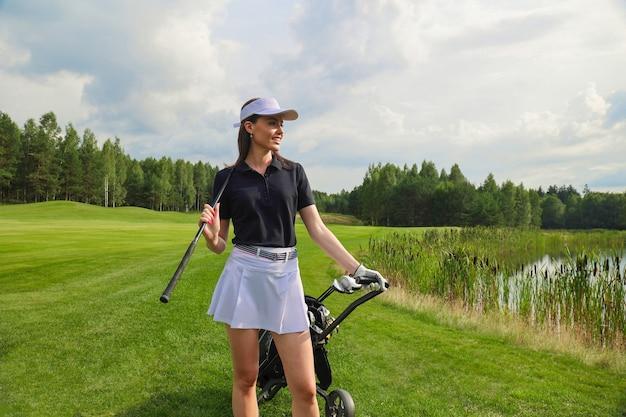 Женщина в стильном летнем костюме для гольфа гуляет с сумкой водителей по красивому зеленому полю для игры в гольф.