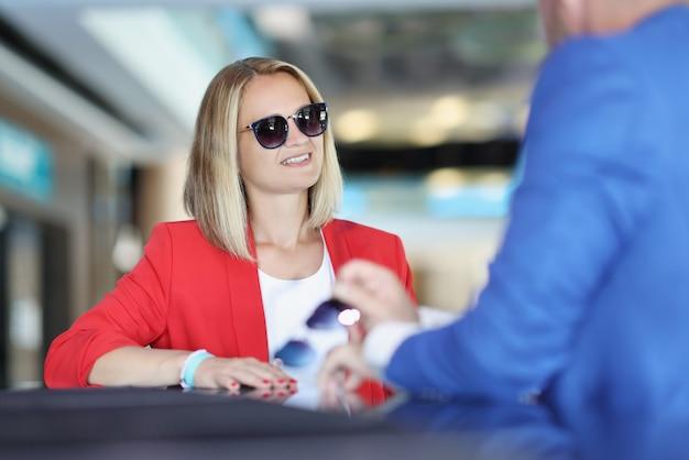 Женщина в костюме и солнцезащитных очках общается с мужчиной
