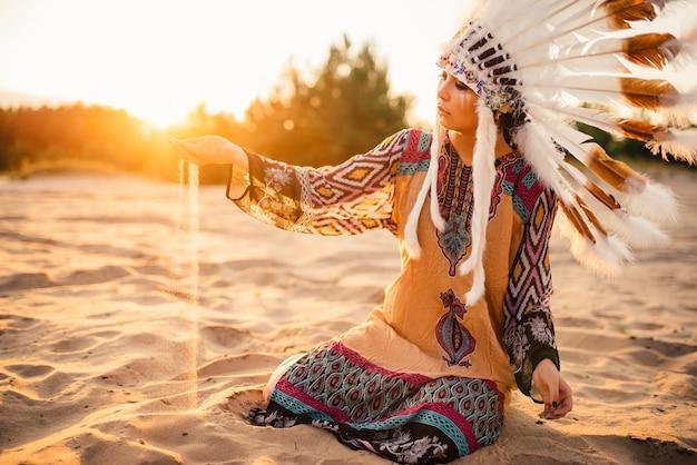 日没時にアメリカインディアンのスーツを着た女性