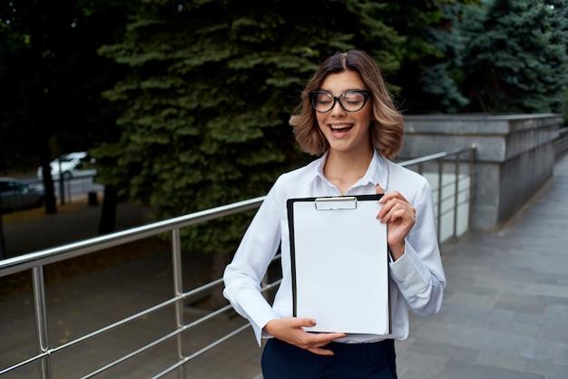 公式の仕事の成功の仕事の明るい背景の外でスーツを着た女性。高品質の写真