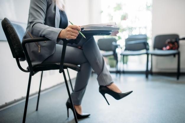 Женщина в костюме проходит собеседование в деловом офисе.