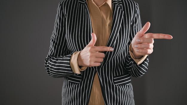 정장을 입은 여성은 옆으로 두 손가락을 보여줍니다. 고품질 사진