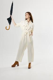 雨からの手の保護のスーツ傘の女性