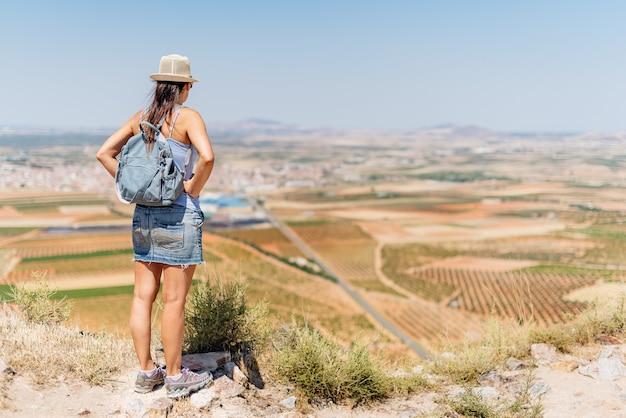 Женщина в летней одежде стоит, созерцая пейзаж полей с оливковыми деревьями и деревню на заднем плане в толедо, испания