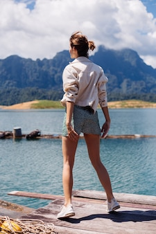 Женщина в летнем платье и куртке туристическое путешествие в таиланд, национальный парк кхао сок, изумительный вид на лодки и озеро.