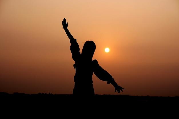 眺めを楽しんで屋外に立っている彼女の手を上げる夏のドレスの女性