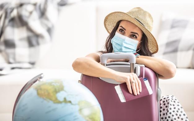 Женщина в летней шляпе и маске прислоняется к чемодану с билетом на самолет и паспортом, думая о путешествии во время пандемии.