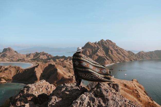 丘と海を背景に岩山の頂上に立っている夏の帽子とカインソンケットの女性