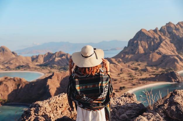 Женщина в летней шляпе и белом платье, наслаждаясь видом на море с вершины холма
