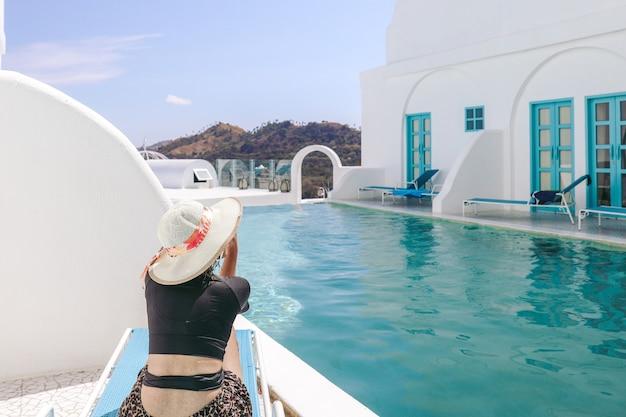 수영장 옆에서 일광욕을 하는 동안 편안한 의자에 앉아 있는 여름 모자를 쓴 여자