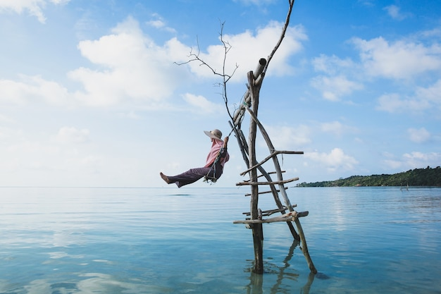 美しい青い空を背景にカリムンジャワ島の浅くて穏やかな海水の上で木製のスイングでスイングする夏の帽子の女性