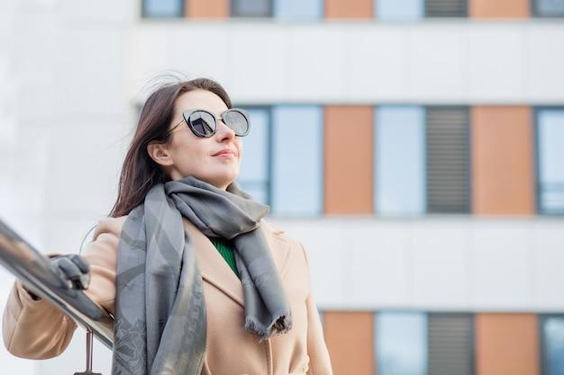 サングラスとコートを着た女性が秋市に立っています。