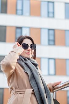 橋の上に立っているサングラスとコートの女性。秋市にて