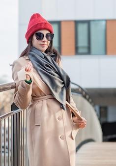 サングラス、赤い帽子とコートの女性がatumn市の橋の上に立っています